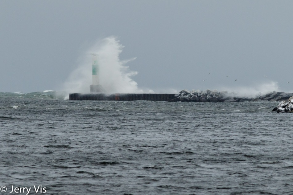 A wave crashing over the harbor light at Muskegon